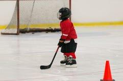 El niño joven que lleva en el casco rojo del hockey del equipo del hockey, patines, guantes el palillo está jugando a hockey fotos de archivo