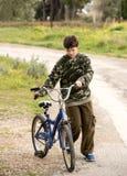 El niño joven se vistió en ropa del ejército con una bicicleta en un paseo adentro Imagenes de archivo