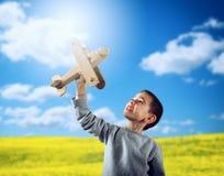 El niño juega con un aeroplano de madera del juguete fotografía de archivo