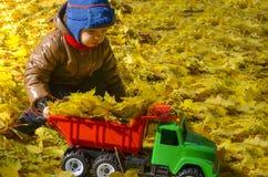 El niño juega con una máquina del juguete en parque del otoño fotos de archivo