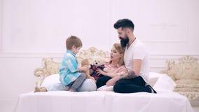 El niño, la mamá y el papá se sientan en cama, sonriendo y comunican Pares felices jovenes junto en dormitorio Familia joven que  almacen de video