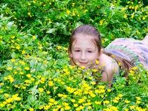 El niño la muchacha tiene un resto en un claro Imagen de archivo libre de regalías