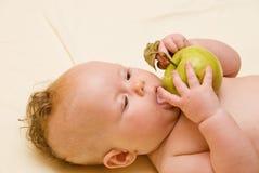 El niño lame la manzana imagen de archivo