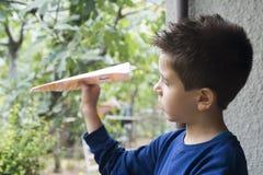 El niño lanza el avión de papel Imagenes de archivo