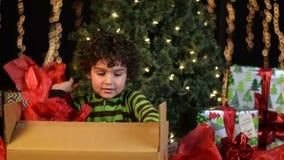 El niño lindo abre el regalo de Navidad almacen de video