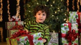 El niño lindo aprensivo abre el regalo de Navidad almacen de video