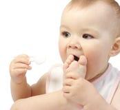 El niño lindo con la cuchara aspira su pie imagen de archivo libre de regalías