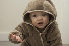 El niño lindo de 9 meses en sudadera con capucha marrón de la piel hace a lo largo del brazo para algo Imagenes de archivo