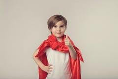 El niño lindo del super héroe da los pulgares para arriba imagen de archivo