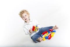 El niño lindo está construyendo con legos Imagen de archivo