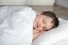 El niño lindo está durmiendo en la cama blanca Fotos de archivo libres de regalías