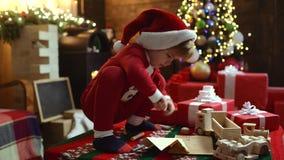 El niño lindo feliz en el sombrero de Papá Noel con presente tiene una Navidad Embrome divertirse cerca del ?rbol de navidad dent almacen de video