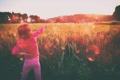 El niño lindo (muchacha) que se colocaba en campo en la puesta del sol con las manos estiró la mirada del paisaje imagen del esti Fotos de archivo