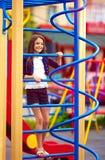 El niño lindo, muchacha sube en el montante en el patio Foto de archivo