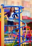 El niño lindo, muchacha sube en el montante en el patio Fotos de archivo