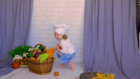El niño lindo puso verduras en cesta Concepto sano de la consumición