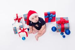 El niño lindo se está sentando en un casquillo del ` s del Año Nuevo entre los juguetes de la Navidad Imagen de archivo