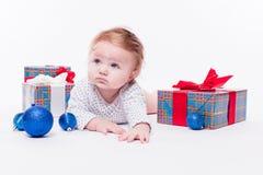 El niño lindo se está sentando en un casquillo rojo del ` s del Año Nuevo en el backgro blanco Fotos de archivo libres de regalías