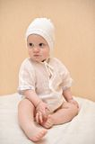 El niño lindo vestido en blanco se sienta en el touchi de la cama imagenes de archivo