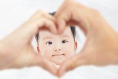 El niño lindo y sonriente con los padres ama las manos