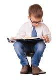 El niño listo lindo en vidrios leyó el cuaderno Imagenes de archivo