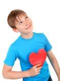 El niño lleva a cabo forma roja del corazón Fotos de archivo