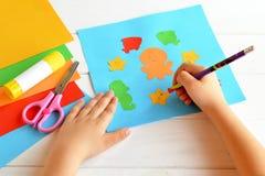 El niño mantiene un lápiz disponible y dibuja Imagenes de archivo