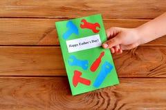 El niño mantiene una tarjeta de felicitación su mano Imagen de archivo libre de regalías