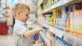 El niño masculino busca productos del ` s del niño en mercado grande almacen de metraje de vídeo