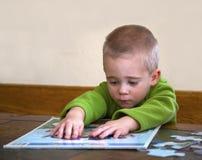 Niño que trabaja en un rompecabezas. Foto de archivo