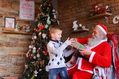 El niño masculino curioso recibe el regalo de Santa Claus en f adornada Foto de archivo libre de regalías