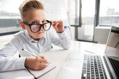 El niño masculino elegante está trabajando en oficina Imagen de archivo