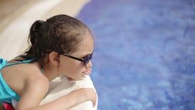 El niño miente en un ocioso del sol por la piscina en el hotel metrajes