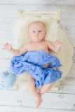 El niño miente en un pequeño material suave azul envuelto de la cama de bebé Fotos de archivo