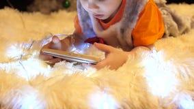 El niño miente en una manta blanca suave en el cuarto de niños Él está mirando historietas en el smartphone Navidad almacen de metraje de vídeo