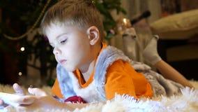 El niño miente en una manta blanca suave en el cuarto de niños Él está mirando historietas en el smartphone Navidad metrajes