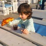 El niño mira el bocadillo, y el bocadillo el niño foto de archivo