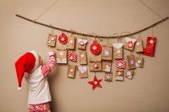 El niño mira el calendario del advenimiento El bebé en un sombrero y pijamas de la Navidad muestra en el primer regalo imagenes de archivo