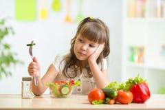 El niño mira con el repugnancia para la comida foto de archivo libre de regalías