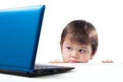 El niño mira el ordenador fotografía de archivo
