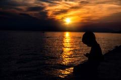 El niño mira en el smartphone en el fondo de una puesta del sol hermosa foto de archivo