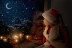 El niño mira hacia fuera la ventana encendido fotos de archivo