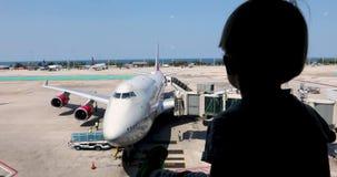 El niño mira la preparación de los aviones para el vuelo metrajes