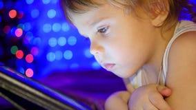 El niño mira a la tableta que miente en cama En el fondo, las luces y las guirnaldas del abeto de la Navidad metrajes