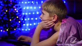 El niño mira a la TV que miente en cama En el fondo, las luces del bokeh y las guirnaldas del abeto de la Navidad metrajes