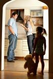 El niño mira a los padres que juran Foto de archivo libre de regalías