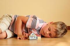 El niño mira modelo una casa Foto de archivo libre de regalías