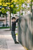 El niño mira a través del agujero en la cerca Imagenes de archivo