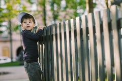 El niño mira a través del agujero en la cerca Imagen de archivo libre de regalías