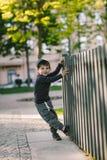 El niño mira a través del agujero en la cerca Fotografía de archivo libre de regalías